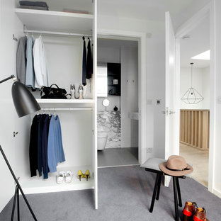 Inspiration for a mid-sized contemporary gender-neutral carpeted and gray floor walk-in closet remodel in London with open cabinets and white cabinets