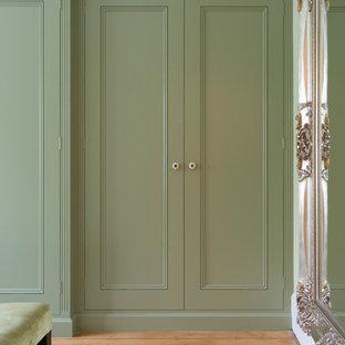 Diseño de vestidor unisex, clásico renovado, grande, con armarios con rebordes decorativos, puertas de armario verdes y suelo de madera clara