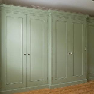 Imagen de vestidor unisex, clásico renovado, grande, con puertas de armario verdes, suelo de madera clara y armarios con paneles empotrados