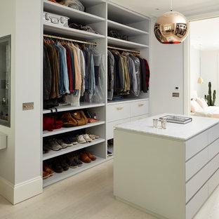 Diseño de vestidor unisex, actual, grande, con armarios con paneles lisos, puertas de armario blancas, suelo de madera clara y suelo beige