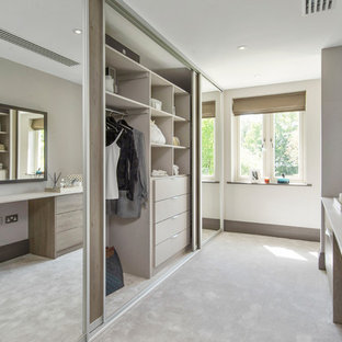 This is an example of a contemporary gender neutral walk-in wardrobe in London with carpet, flat-panel cabinets, light wood cabinets and beige floors.
