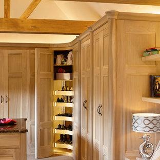 Immagine di un ampio spazio per vestirsi unisex moderno con ante con riquadro incassato, ante in legno chiaro e moquette