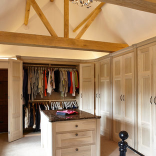 This is an example of an expansive modern gender neutral dressing room in Surrey with recessed-panel cabinets, light wood cabinets and carpet.