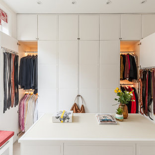 Inspiration for a contemporary gender neutral dressing room in London with white cabinets.