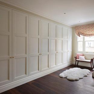 ロンドンの広い男女兼用ヴィクトリアン調のおしゃれな壁面クローゼット (落し込みパネル扉のキャビネット、白いキャビネット、濃色無垢フローリング、茶色い床) の写真