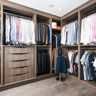 Photo of a large contemporary walk-in wardrobe for men in Buckinghamshire with medium wood cabinets, brown floors, open cabinets and dark hardwood flooring.