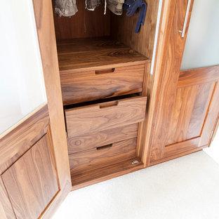 Diseño de armario vestidor unisex, moderno, grande, con puertas de armario de madera en tonos medios y moqueta