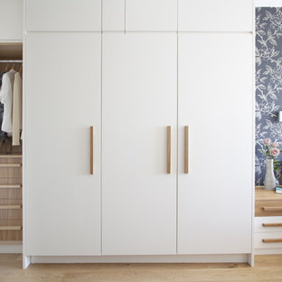 Photo of a contemporary standard wardrobe in London with white cabinets.