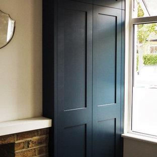 Imagen de armario unisex, clásico, de tamaño medio, con armarios estilo shaker, puertas de armario azules y suelo de madera oscura