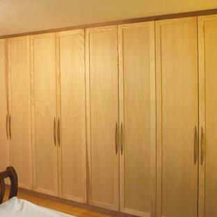 Foto di un armadio o armadio a muro unisex con ante con riquadro incassato e ante in legno chiaro