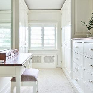 Immagine di uno spazio per vestirsi unisex country di medie dimensioni con ante con bugna sagomata, ante bianche, moquette e pavimento beige