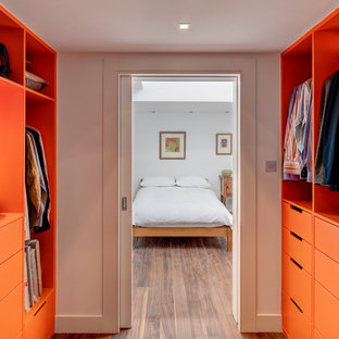 Example of a trendy gender-neutral dark wood floor and brown floor walk-in closet design in London with flat-panel cabinets and orange cabinets
