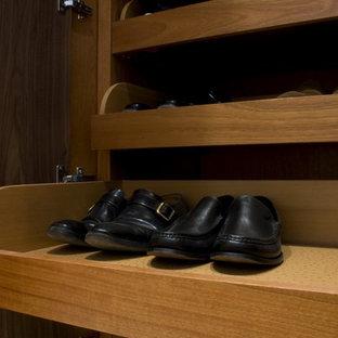 Ejemplo de armario vestidor de hombre, clásico, grande, con armarios con rebordes decorativos y puertas de armario de madera oscura
