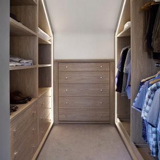 Foto de armario vestidor de hombre, actual, de tamaño medio, con armarios abiertos, puertas de armario de madera oscura, moqueta y suelo marrón