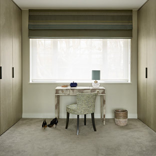 This is an example of a medium sized contemporary dressing room for women in London with carpet, flat-panel cabinets, brown cabinets and grey floors.