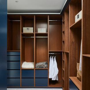 Diseño de armario vestidor unisex, moderno, con armarios con paneles lisos, puertas de armario azules, moqueta y suelo gris