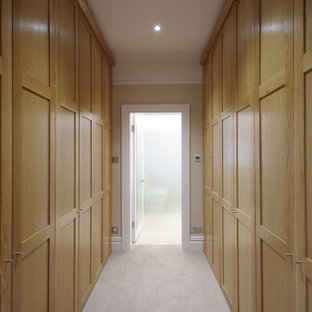 Ispirazione per uno spazio per vestirsi unisex moderno di medie dimensioni con ante in stile shaker, ante in legno scuro e moquette
