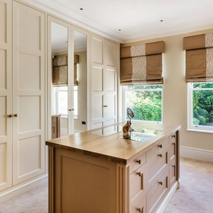 Traditional gender neutral dressing room in Surrey with recessed-panel cabinets, beige cabinets, carpet and beige floors.