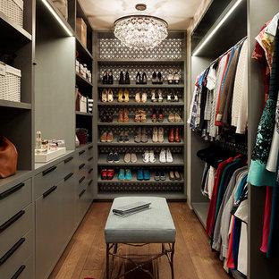Inredning av ett eklektiskt walk-in-closet för kvinnor, med släta luckor, gröna skåp, mellanmörkt trägolv och brunt golv
