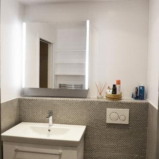 Idée de décoration pour un petit WC et toilettes design avec un WC suspendu, des carreaux de céramique, un mur gris, un sol en carrelage de céramique, une grande vasque et un sol gris.