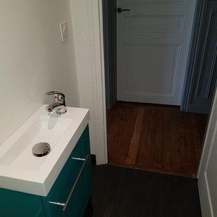Стильный дизайн: маленький туалет в современном стиле с плоскими фасадами, бирюзовыми фасадами, черной плиткой, керамической плиткой, черными стенами, полом из керамической плитки, подвесной раковиной, столешницей из плитки и черным полом - последний тренд