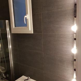 Esempio di un piccolo bagno di servizio minimal con ante lisce, ante turchesi, piastrelle nere, piastrelle in ceramica, pareti nere, pavimento con piastrelle in ceramica, lavabo sospeso, top piastrellato e pavimento nero