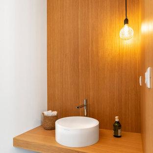Inspiration pour un WC et toilettes design en bois avec un plan de toilette en bois, un mur blanc, une vasque et un sol gris.