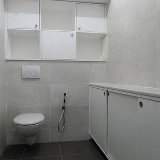 Cette photo montre un petit WC et toilettes chic avec des portes de placard blanches, un WC suspendu, un carrelage beige, un mur beige, un sol en carreau de terre cuite, un lavabo intégré, un plan de toilette en stratifié et un placard à porte plane.