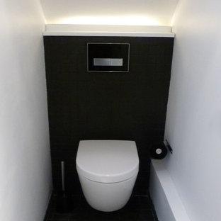 Ejemplo de aseo actual, pequeño, con sanitario de pared, baldosas y/o azulejos negros, baldosas y/o azulejos de terracota, paredes blancas, suelo de baldosas de terracota y suelo negro