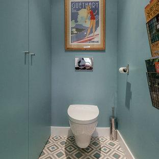 Diseño de aseo actual, de tamaño medio, con puertas de armario azules, sanitario de pared, paredes azules y suelo de baldosas de cerámica