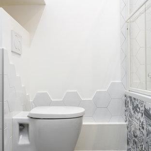 Inspiration pour un petit WC et toilettes design avec un WC suspendu, un carrelage blanc, un sol gris, un placard à porte plane, des portes de placard blanches, des carreaux de céramique, un mur blanc, un sol en carrelage de céramique et un plan de toilette blanc.