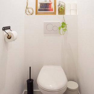 Foto di un bagno di servizio minimal di medie dimensioni con WC sospeso, pistrelle in bianco e nero, pareti bianche e pavimento in cementine