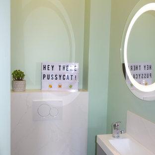Idee per un piccolo bagno di servizio contemporaneo con WC sospeso, piastrelle bianche, piastrelle di marmo, pareti verdi, pavimento con piastrelle in ceramica, lavabo sospeso, pavimento nero, top bianco, ante lisce, ante grigie e top in quarzite