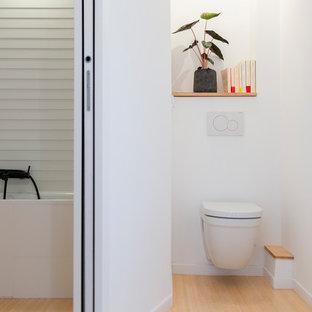 На фото: туалет в современном стиле с фасадами с утопленной филенкой, инсталляцией, белыми стенами, полом из бамбука и столешницей из дерева с