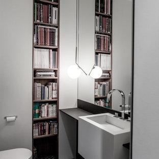 На фото: большой туалет в современном стиле с инсталляцией, черно-белой плиткой, белыми стенами, полом из керамической плитки, подвесной раковиной, столешницей из искусственного камня и открытыми фасадами с
