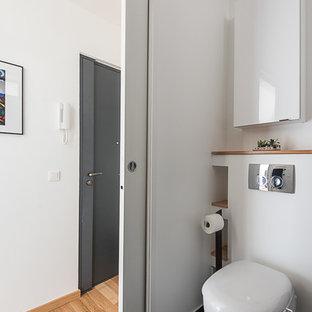 Inspiration pour un petit WC et toilettes design avec un placard à porte plane, des portes de placard blanches, un WC suspendu, un mur blanc, un plan de toilette en bois et un sol gris.