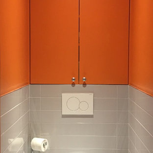 Photo of a small contemporary cloakroom in Paris with a wall mounted toilet, ceramic tiles, orange walls, ceramic flooring, grey floors and orange worktops.
