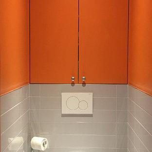 Esempio di un piccolo bagno di servizio contemporaneo con WC sospeso, piastrelle in ceramica, pareti arancioni, pavimento con piastrelle in ceramica, pavimento grigio e top arancione