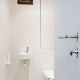 Foto di un piccolo bagno di servizio chic con WC sospeso, pareti beige, pavimento in terracotta, lavabo sospeso, pavimento multicolore e top bianco