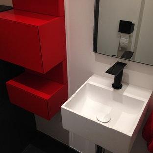 Idée de décoration pour un WC et toilettes de taille moyenne avec un placard à porte affleurante, des portes de placard rouges, un WC suspendu, un carrelage noir, des carreaux de céramique, un mur blanc, un sol en carrelage de céramique, un lavabo suspendu, un plan de toilette en surface solide et un sol noir.