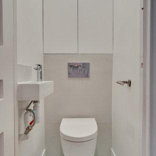 Идея дизайна: маленький туалет в стиле модернизм с фасадами с декоративным кантом, белыми фасадами, инсталляцией, серой плиткой, цементной плиткой, зеленым полом, серыми стенами и полом из цементной плитки