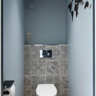 Aménagement d'un très grand WC et toilettes scandinave avec un WC suspendu, des carreaux de béton, un mur bleu, un sol en bois clair et un plan de toilette blanc.