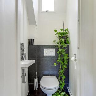 Inspiration pour un WC et toilettes design de taille moyenne avec un lavabo suspendu, un WC suspendu, un carrelage noir et un mur blanc.