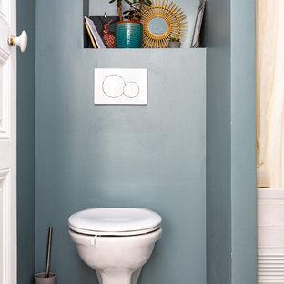 Imagen de aseo nórdico, pequeño, con sanitario de pared, paredes azules, suelo de azulejos de cemento y suelo multicolor