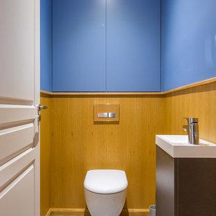 Idée de décoration pour un WC et toilettes design de taille moyenne avec un WC suspendu, un mur bleu et un lavabo posé.