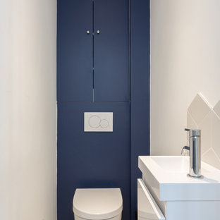 This is an example of a small contemporary cloakroom in Paris with beaded cabinets, blue cabinets, a wall mounted toilet, white tiles, ceramic tiles, blue walls, cement flooring, a wall-mounted sink, yellow floors and white worktops.