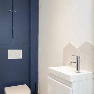 Exemple d'un petit WC et toilettes tendance avec un placard à porte affleurante, des portes de placard bleues, un WC suspendu, un carrelage blanc, des carreaux de céramique, un mur bleu, un sol en carreaux de ciment, un lavabo suspendu, un sol jaune et un plan de toilette blanc.