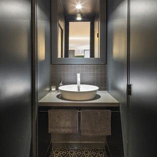 На фото: большой туалет в современном стиле с черной плиткой, керамической плиткой, черными стенами, полом из цементной плитки, накладной раковиной, столешницей из ламината и черным полом с