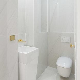 Inspiration pour un WC et toilettes design de taille moyenne avec un WC suspendu, un carrelage blanc, des carreaux de céramique, un mur blanc, un sol en carrelage de céramique, un sol blanc et une vasque.