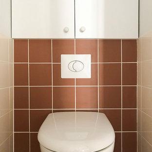 Идея дизайна: маленький туалет в современном стиле с фасадами с декоративным кантом, белыми фасадами, инсталляцией, коричневой плиткой, керамической плиткой, белыми стенами, полом из керамической плитки и бежевым полом